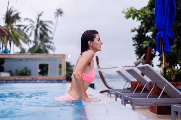 Молодая счастливая стройная европейская женщина в ярко-розовом бикини и синем бассейне