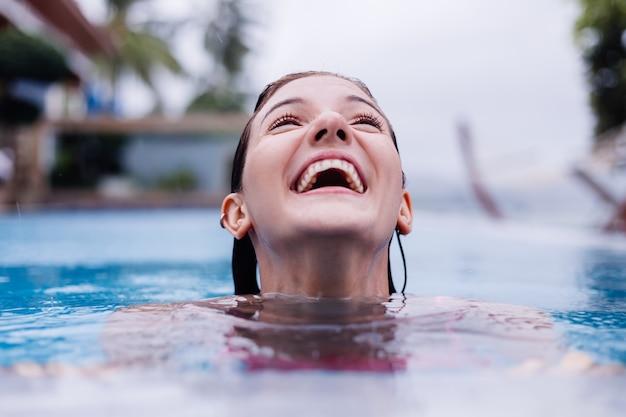 明るいピンクのビキニブルーのスイミングプールで若い幸せなフィットスリムなヨーロッパの女性