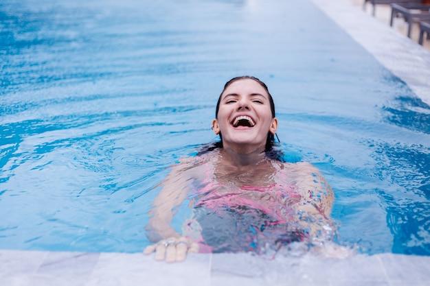 밝은 분홍색 비키니 파란색 수영장에서 젊은 행복 맞는 슬림 유럽 여자