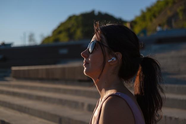선글라스를 쓴 젊은 행복한 피트니스 여성은 도시에서 야외 운동을 마칩니다. 휴식을 취하다. 이어폰으로 음악을 감상하세요. 일몰. 건강한 생활. 자유. 컨투어 라이트.