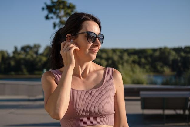 선글라스를 쓴 젊은 행복한 피트니스 여성은 도시에서 달리기를 마칩니다. 이어폰 끼기. 휴식을 취하다. 이어폰으로 음악을 감상하세요. 일몰. 건강한 생활. 자유. 야외 운동.