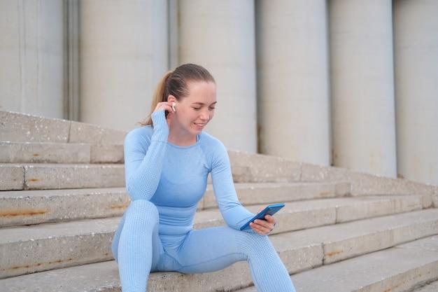 젊은 행복한 피트니스 여성이 앉아서 도시에서 달리기를 마칩니다. 전화를 들고 헤드폰으로 음악을 들을 수 있습니다. 일몰. 건강한 생활. 자유. 야외 운동. 고품질 사진