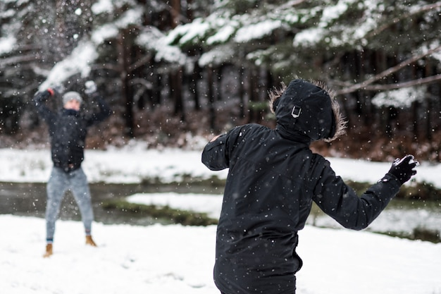 Молодые счастливые друзья, наслаждаясь бросать снежки Premium Фотографии
