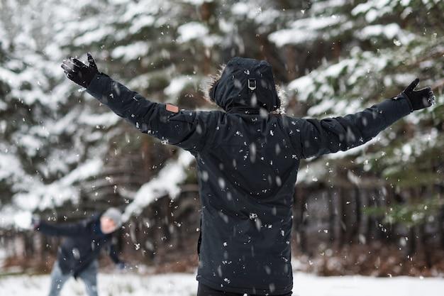 Молодые счастливые друзья, наслаждаясь бросать снежки