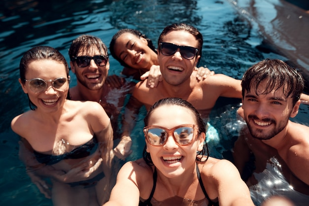 Young happy friends in outdoor swimming pool