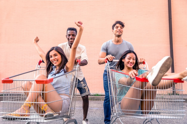 Young happy friends running with shopping carts