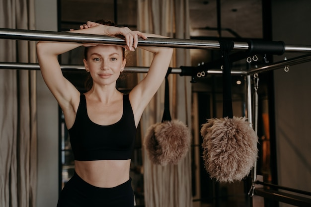 Young happy ginger woman in black sportswear taking break on pilates machine between trainings in gym,joyfully looking forward smiling on camera, healthy lifestyle and sport indoors concept