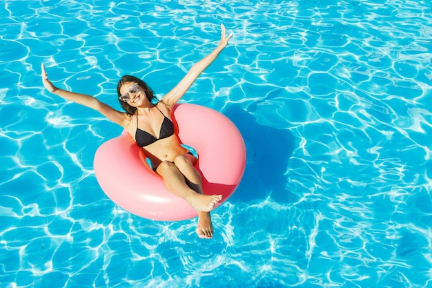 Young happy girl in bikini is swimming in the pool with a pink circle