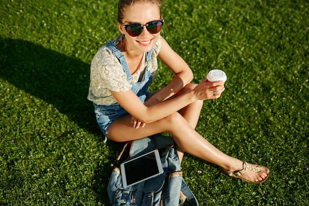 若い幸せな女の子は草の上に座って屋外でコーヒーを飲みます
