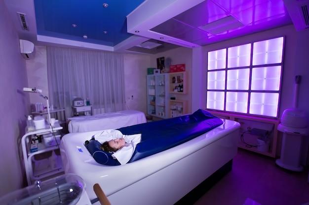 Молодая счастливая девушка наслаждается процедурой обертывания и гидромассажем в спа-салоне.