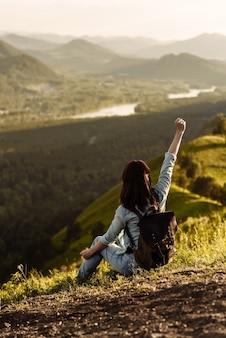 Молодая счастливая девушка-путешественница с рюкзаком в горах сидит и смотрит на долину