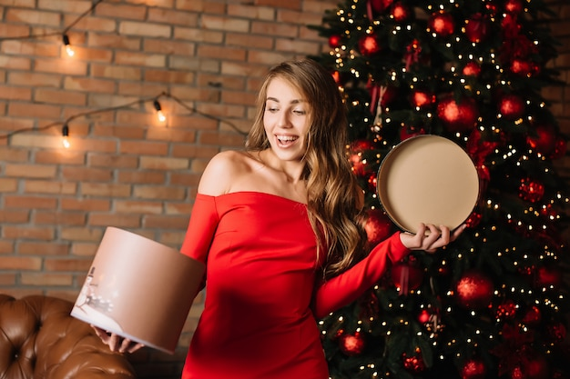 Young happy girl holding gift box in hands.new year present, winter shopping