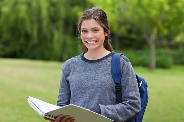 大きな笑顔を見せながら公園に彼女のノートを持っている若い幸せな女の子