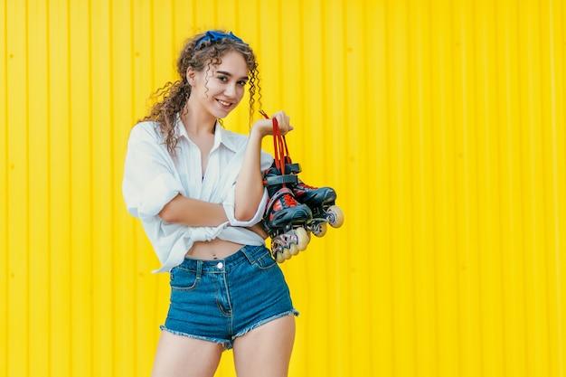Молодая счастливая девушка держит ролики на желтой стене