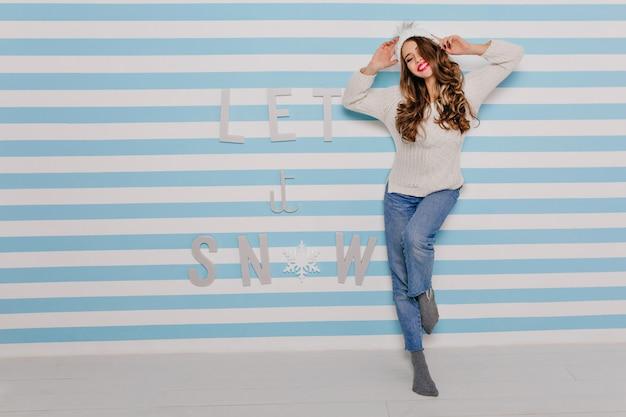 うれしそうな気分の若い、幸せな女の子は、壁に美しい碑文で居心地が良いと感じています。明るい口紅と心から笑顔のブルネット