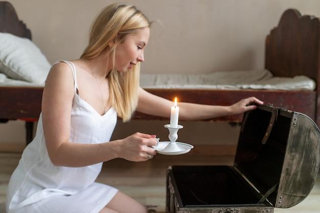 Молодая счастливая девушка в ночнушке со свечой в руке открывает старый деревянный сундук