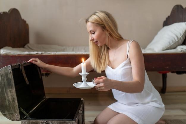 Молодая счастливая девушка в nightie со свечой в ее руке, открывая старый деревянный сундук.