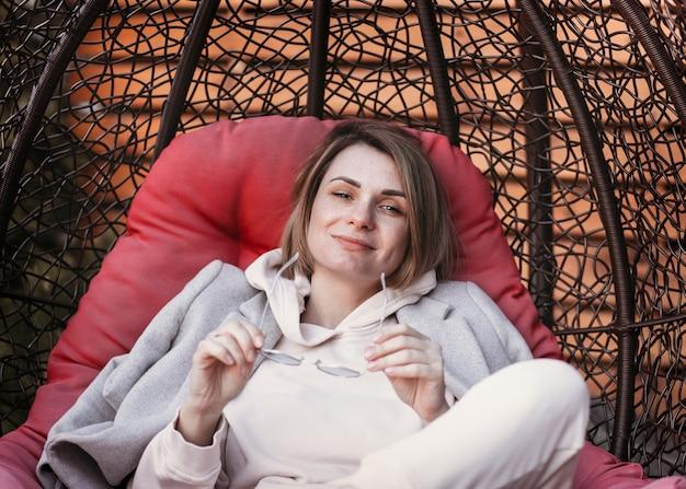 Молодая счастливая девушка в солнцезащитных очках наслаждается отдыхом на природе в кресле