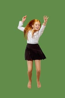 Молодая счастливая девушка прыгает в воздухе