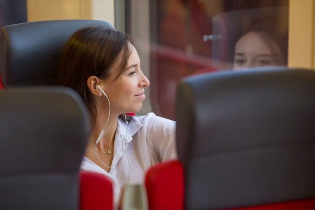 Young happy girl listening music traveling by train