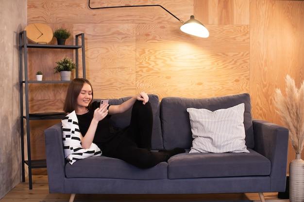 Молодая счастливая девушка лежа на софе с телефоном.