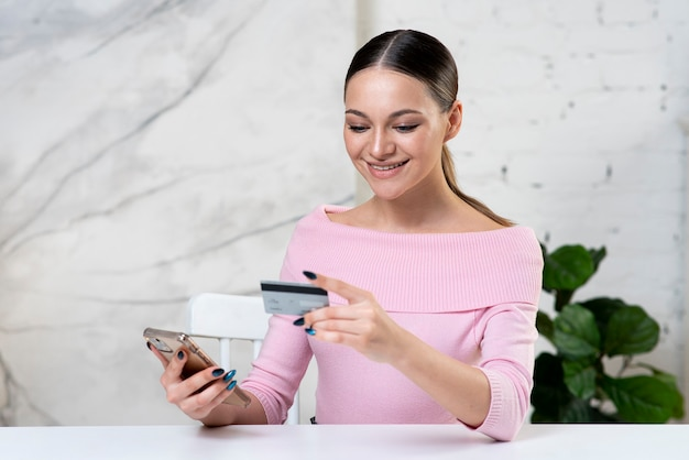 Young happy girl, positive woman looking at credit bank card paying online in shop, enter