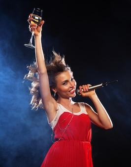 Молодая счастливая девушка поет в микрофон на вечеринке