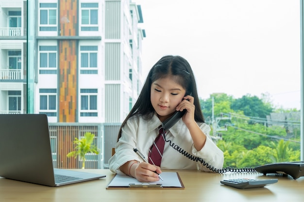 Young happy girl sitting on office desk playing acting as a businesswoman