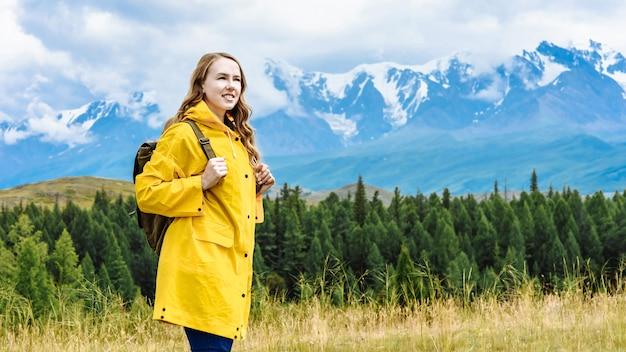 눈 덮인 알프스 산맥의 배경에 배낭 젊은 행복 소녀 관광. 여행 및 휴가 개념