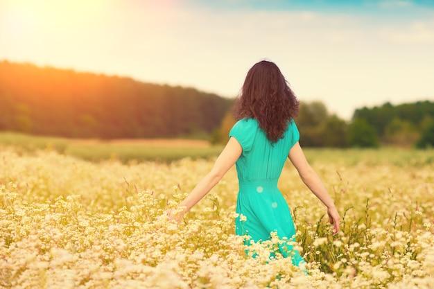 花の牧草地を歩く若い幸せな女の子