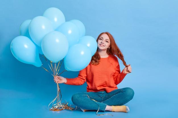 Молодая счастливая девушка с букетом гелиевых шаров сидит на полу со скрещенными ногами, трогает ее волосы