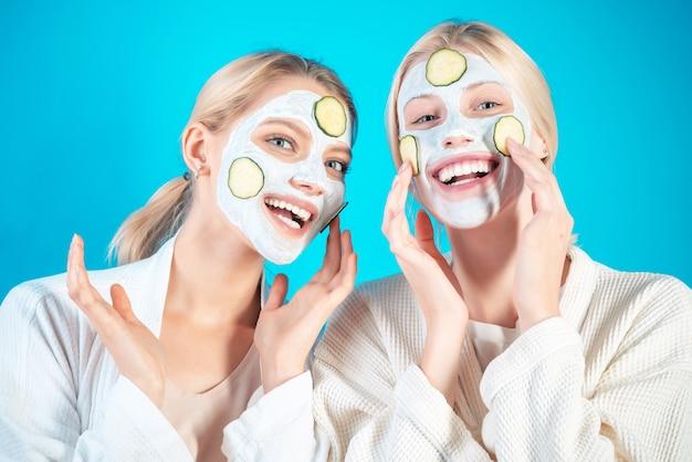 若い幸せな女の子は青のキュウリのスライスで顔のマスクを行う