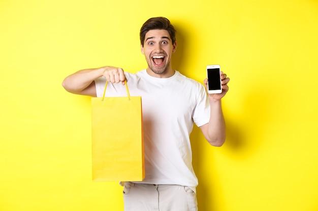 쇼핑백을 들고 스마트 폰 화면, 노란색 벽을 보여주는 젊은 행복한 사람