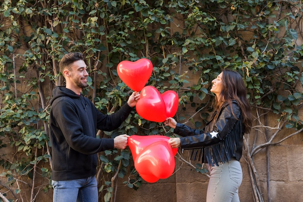 Young happy guy and smiling lady holding balloons in form of hearts