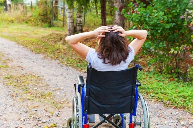 자유를 즐기는 병원 공원에서 휠체어에 젊은 행복 한 핸디캡 여자. 야외에서 장애인을 위한 잘못된 의자에 마비된 소녀. 재활 개념입니다.