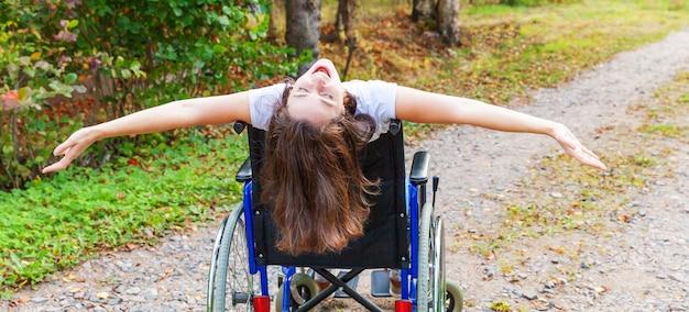 Молодая счастливая женщина-инвалид в инвалидной коляске на дороге в больничном парке, наслаждаясь свободой