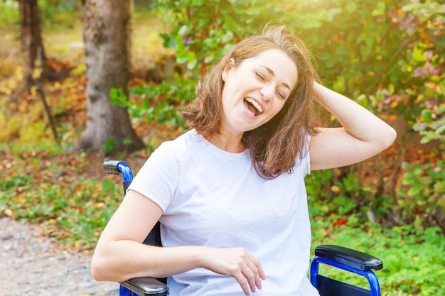 자연 속에서 야외 휠체어에 젊은 행복 한 핸디캡 여자