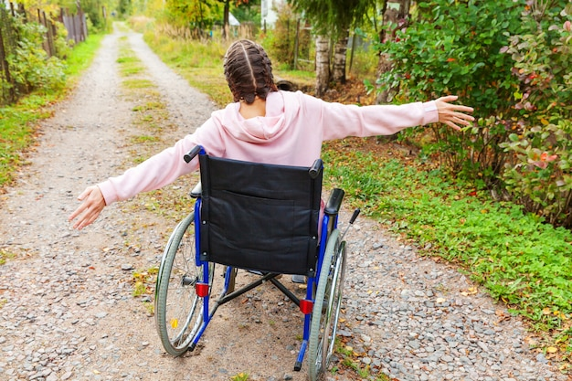 Young happy handicap woman in wheelchair on road in hospital park enjoying freedom. paralyzed girl in invalid chair for disabled people outdoor in nature. rehabilitation concept.