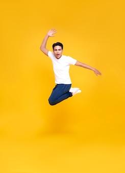 노란색 위로 점프 젊은 행복 잘 생긴 아시아 남자.