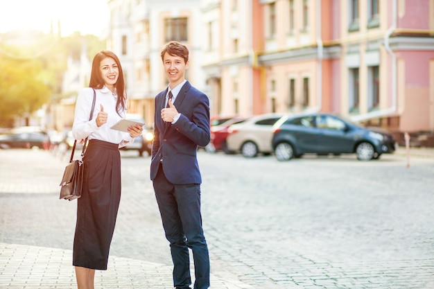 Young happy handsome business man and woman gesturing thumb up business success concept in city