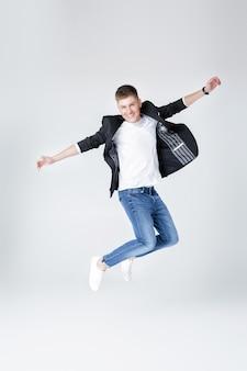 청바지와 재킷 점프에서 젊은 행복 잘 생긴 남자