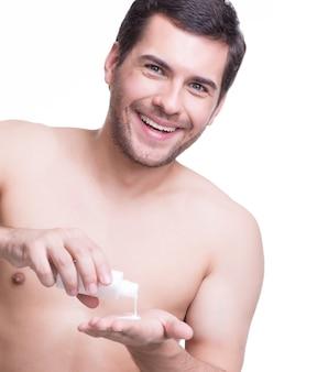 Il giovane uomo bello felice versa la lozione sulla sua mano - isolata su bianco.