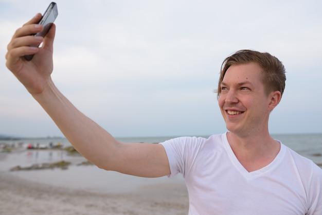 Молодой счастливый красивый мужчина улыбается во время съемки селфи