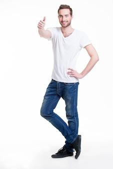 Il giovane uomo bello felice con i pollici aumenta il segno in casuals in piena crescita - isolato su bianco.