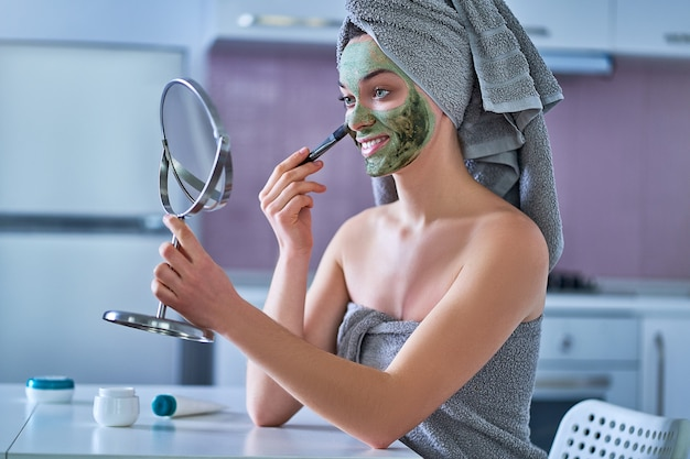 Young happy healthy female in bath towel applying cleansing face clay mask during spa day at home using brush and small table mirror. face skin care