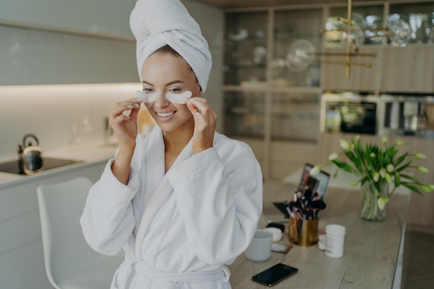 Young happy healthy woman in bathrobe and towel turban on head taking off collagen hydrogel beauty patches and smiling while doing beauty or cosmetic procedures at home. personal care concept