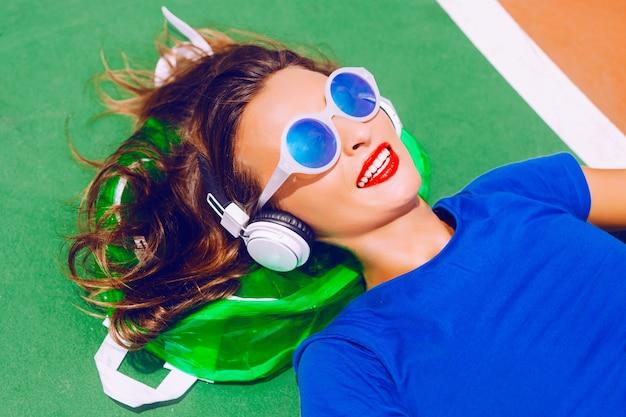 彼女の明確なネオンバックパックに敷設、彼女のお気に入りの音楽を聴いて、夏の休暇と彼女の休暇を楽しむ若い幸せな内気な少女。完璧な白い歯と光沢のある赤い唇。