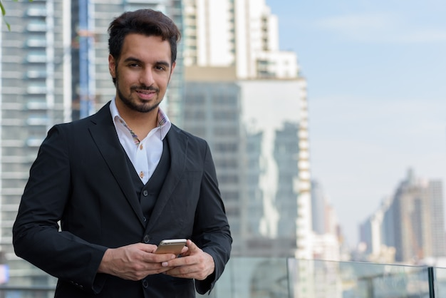 Young happy indian businessman smiling while holding mobile phone at rooftop in bangkok
