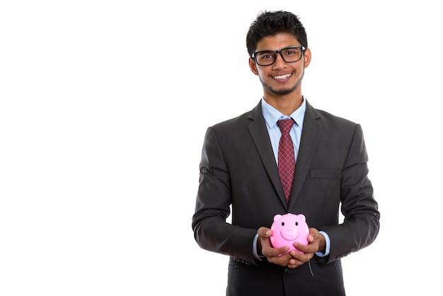 돼지 저금통을 들고 웃 고 젊은 행복 인도 사업가