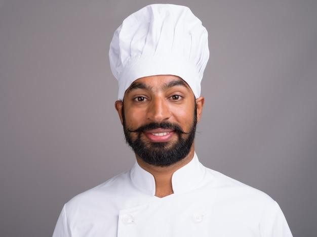 Молодой счастливый индийский шеф-повар на сером
